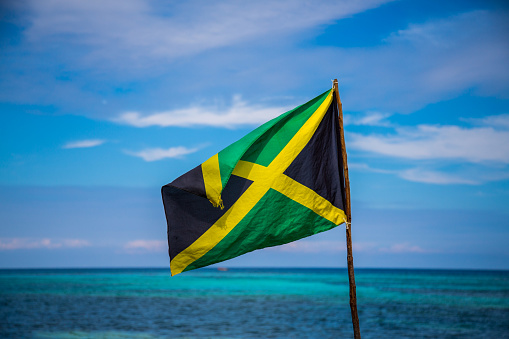 Jamaican flag and turquoise sea on sunny day - gettyimageskorea