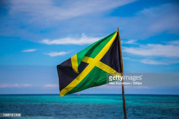 jamaican flag and turquoise sea on sunny day - jamaica stock pictures, royalty-free photos & images