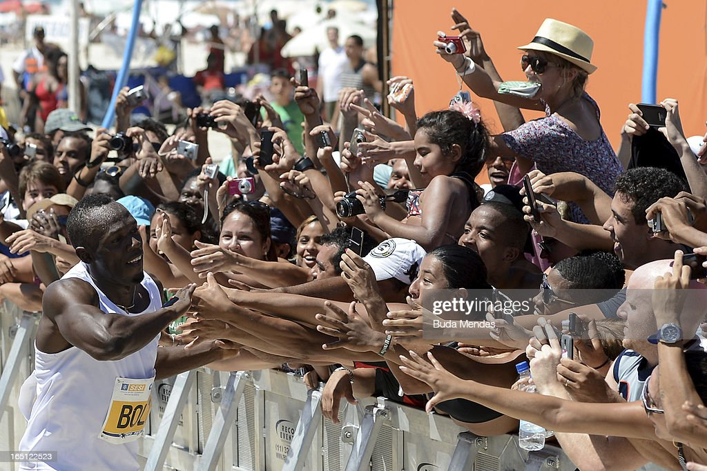 Jamaican Olympic gold medallist Usain Bolt celebrates with fans after winning the 'Mano a Mano' Men's 150m challenge on Copacabana beach on March 31, 2013 in Rio de Janeiro, Brazil.