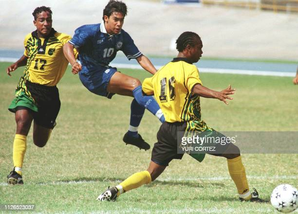 Jamaican players Marco McDonald and Eugene Barnes dispute the ball with Guatamalan player Carlos Ruiz 14 August during the elimination rounds of the...