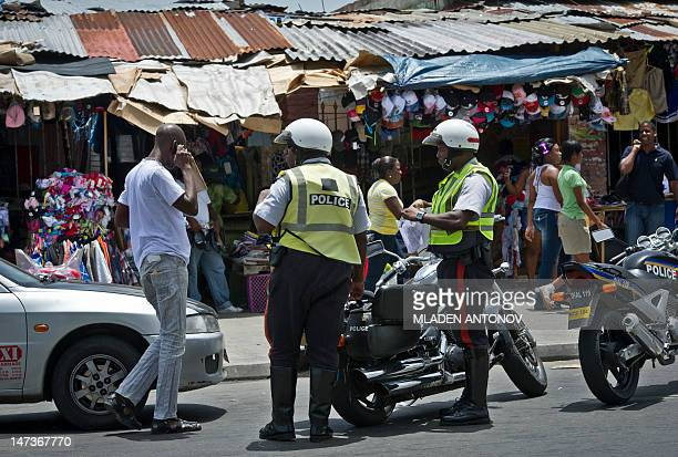 Jamaican policemen talk to a driver on a shopping street in downtown Kingston June 28 2012 Jamaica will celebrate its 50th anniversary as an...