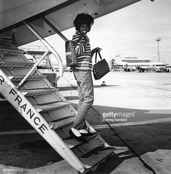 Jamaican pop singer Millie Small who soared into the top twenty with her record 'My Boy Lollipop' at the age of 16 walking down the steps of an Air...