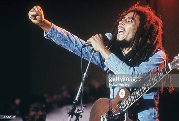 Jamaican Reggae musician, songwriter, and singer Bob Marley performs on stage, in a concert at Grona Lund, Stockholm, Sweden. He extends his fist as...