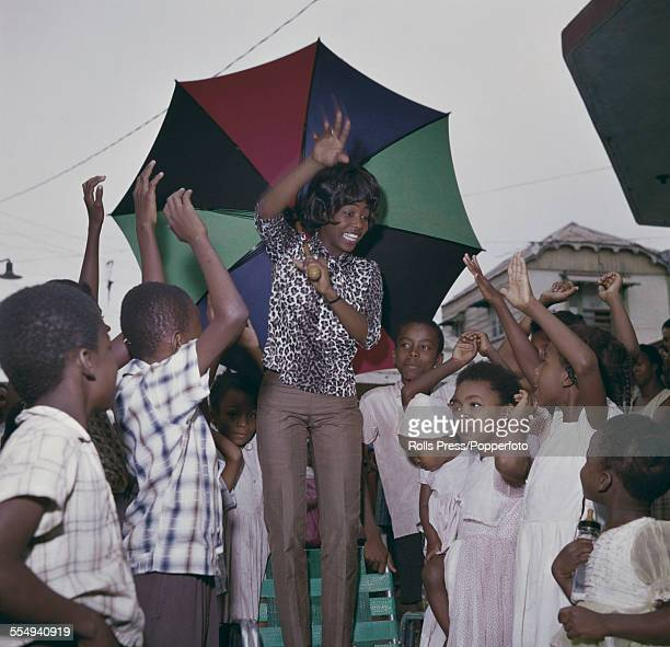 Jamaican singer Millie Small who had an international hit with the song 'My Boy Lollipop' pictured holding a large umbrella with children during a...