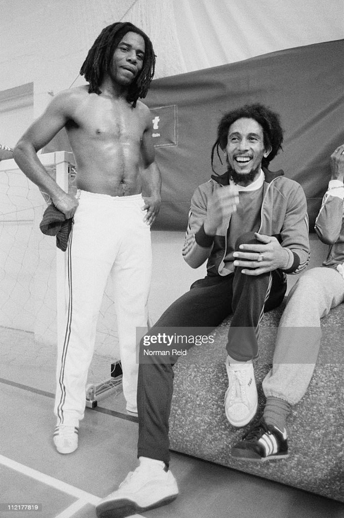 Jamaican singer-songwriter Bob Marley (1945 - 1981, right) takes a break with fellow reggae artist Eddy Grant during an amateur football match, Hammersmith Leisure Centre, London, 16th July 1980.