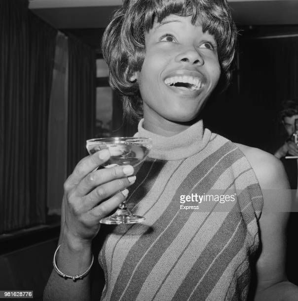 Jamaican singersongwriter Millie Small having a drink before leaving the UK for Ghana at Heathrow Airport London UK 3rd November 1967