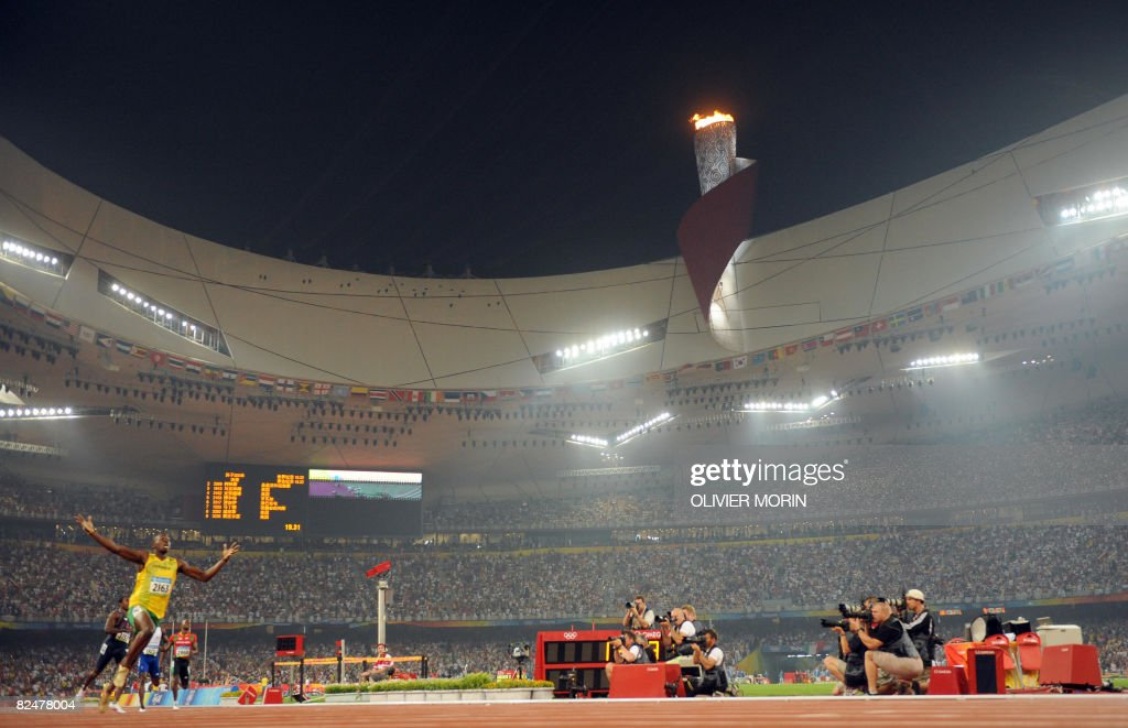 Jamaican sprint satr Usain Bolt raises his arms in victory in the final of the men's 200m at the 'Bird's Nest' National Stadium during the 2008 Beijing Olympic Games on August 20, 2008. Bolt won gold and broke the world record.