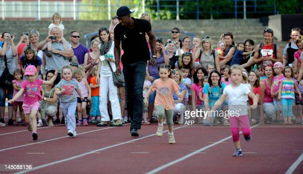 Jamaican sprinter Usain Bolt runs with young girls during a promotional event with children on May 23 2012 prior to the Zlata Tretra athletics...