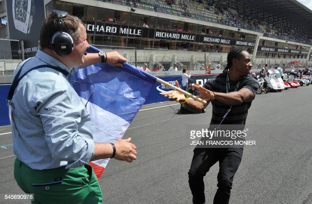 Jamaican sprinter Yohan Blake grabs a French flag from French Le Mans race director Patrick Morisseau prior to give the start of the Little Big Mans...