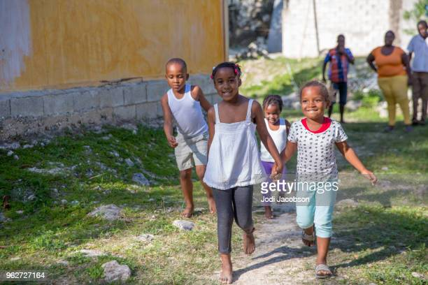 Jamaican woman playing with children outdoors in Saint Irwin, an impoverished village in rural Jamaica