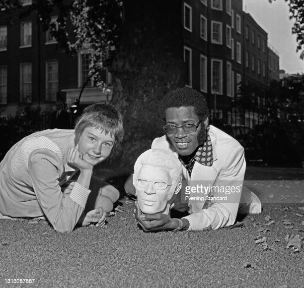 Jamaican-British reggae musician and music producer Dandy Livingstone with Penny Ainskow and a bust of his head, UK, 12th November 1973.