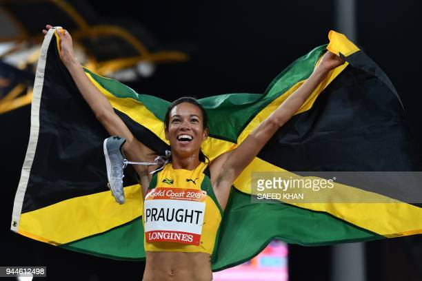 TOPSHOT Jamaica's Aisha Praught celebrates with her flag after winning the athletics women's 3000m steeplechase final during the 2018 Gold Coast...