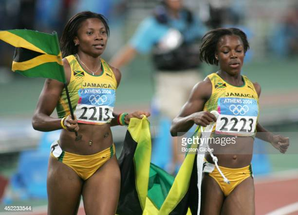 Jamaica's Aleen Bailey left who finished 4th in the 200meter final helps her teammate and gold medal winner Veronica Campbell carry the flag in a...