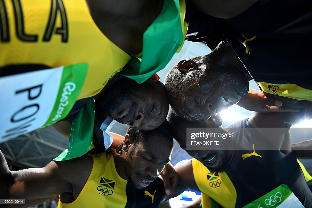 TOPSHOT - (Clockwise from L) Jamaica's Asafa Powell, Jamaica's Yohan Blake, Jamaica's Nickel Ashmeade and Jamaica's Usain Bolt celebrate after they won the Men's 4x100m Relay Final during the athletics event at the Rio 2016 Olympic Games at the Olympic Stadium in Rio de Janeiro on August 19, 2016. / AFP / FRANCK