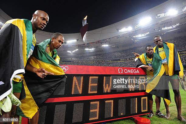 Jamaica's Asafa Powell Michael Frater Nesta Carter and Usain Bolt pose by their world record winning time after the men's 4100m relay final at the...