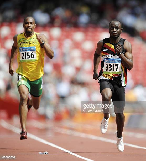 Jamaica's Christopher Williams and Zimbabwe's Brian Dzingai compete in the men's first round 200m heat 2 at the Bird's Nest National Stadium during...