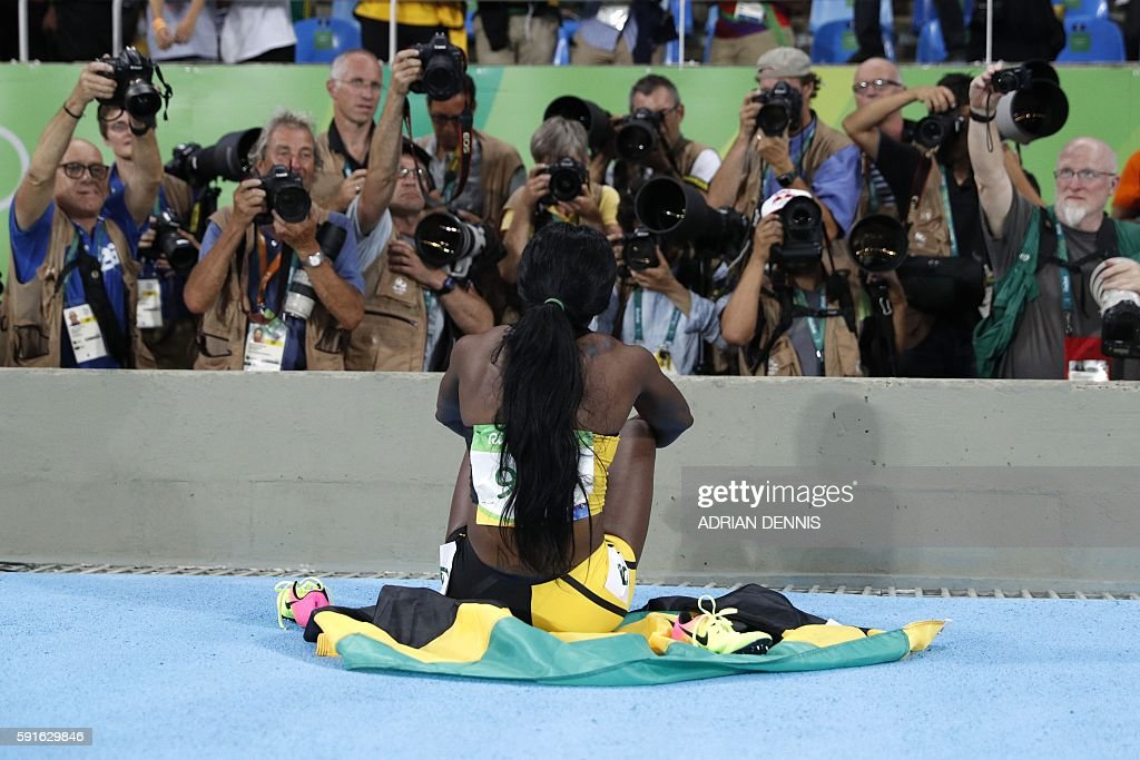 Jamaica's Elaine Thompson celebrates winning the gold medal in the Women's 200m Final during the athletics event at the Rio 2016 Olympic Games at the Olympic Stadium in Rio de Janeiro on August 17, 2016. / AFP / Adrian DENNIS