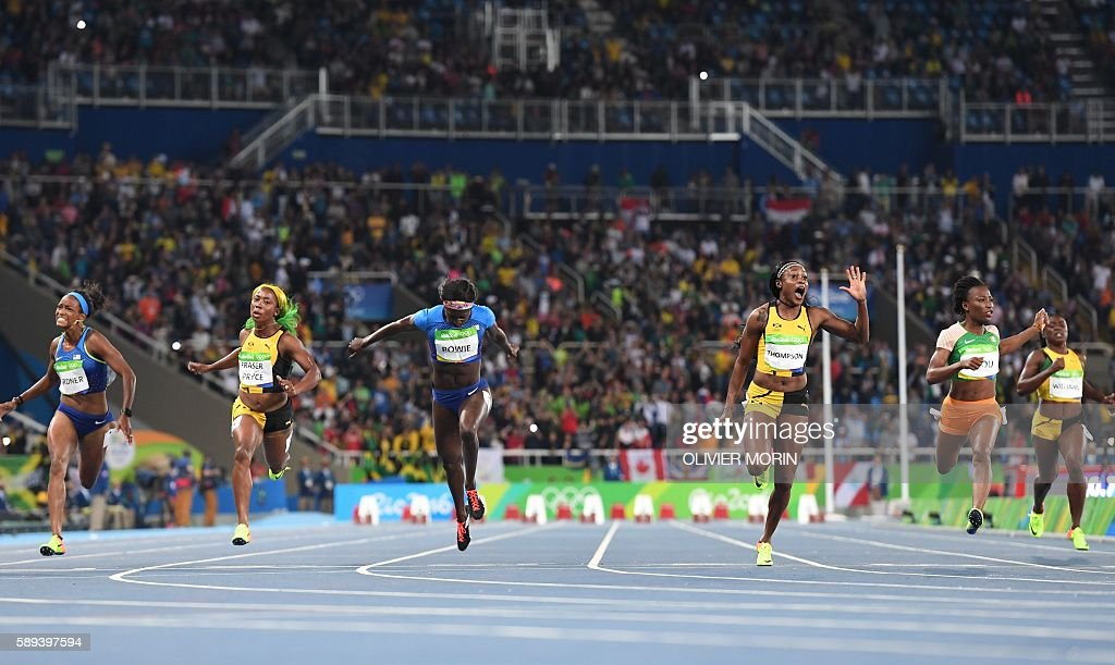 TOPSHOT - Jamaica's Elaine Thompson (3rdR) reacts as she crosses the finish line to win the Women's 100m Final during the athletics event at the Rio 2016 Olympic Games at the Olympic Stadium in Rio de Janeiro on August 13, 2016. / AFP / OLIVIER