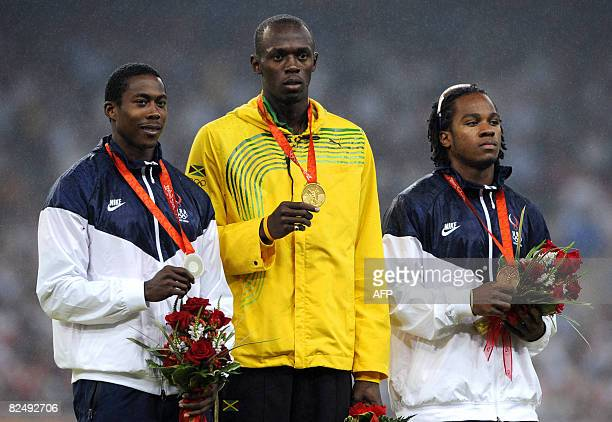 Jamaica's gold medalist Usain Bolt US silver medalist Shawn Crawford and US bronze medalist Walter Dix pose on the podium a day after the men's 200m...