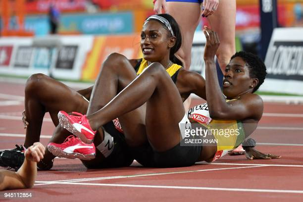 Jamaicas Janieve Russell celebrates with Jamaicas Ronda Whyte after Russell won the athletics women's 400m hurdles final during the 2018 Gold Coast...