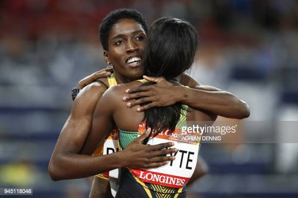 Jamaicas Janieve Russell celebrates with Jamaicas Ronda Whyte after winning the athletics women's 400m hurdles final during the 2018 Gold Coast...