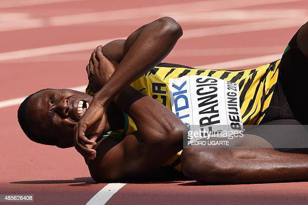 Jamaica's Javon Francis lies injured on the track in the qualifying round of the men's 4x400 metres relay athletics event at the 2015 IAAF World...