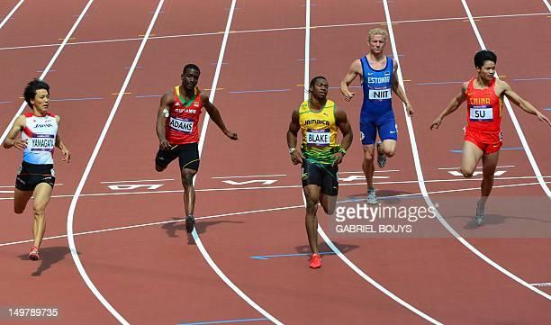 Jamaica's Johan Blake crosses the finish line as he competes with Japan's Ryota Yamagata Saint Kitts Nevis' Antoine Adams Estonia's Marek Niit and...