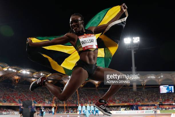 Jamaica's Kimberly Williams holds her national flag as she celebrates winning the athletics women's triple jump final during the 2018 Gold Coast...
