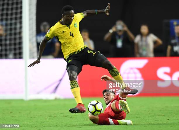 Jamaica's Ladale Richie jumps over Canada's Lucas Cavallini during their 2017 CONCACAF Gold Cup match at the University of Phoenix Stadium on July...