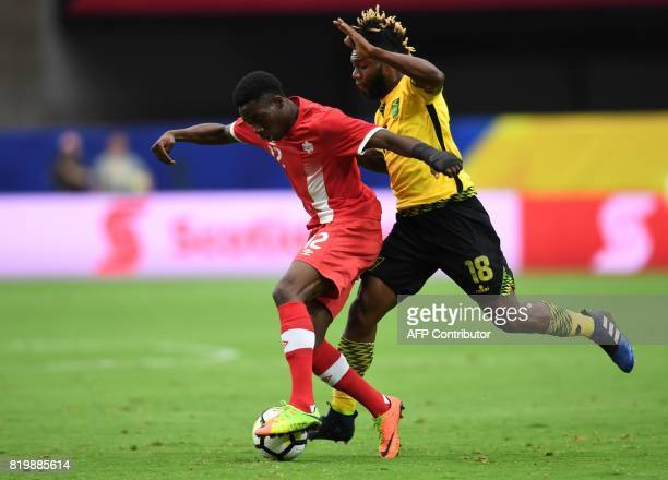 Jamaica's Owayne Gordon vies for the ball with Canada's Alphonso Davies during their CONCACAF tournament quarterfinal match at the University of...