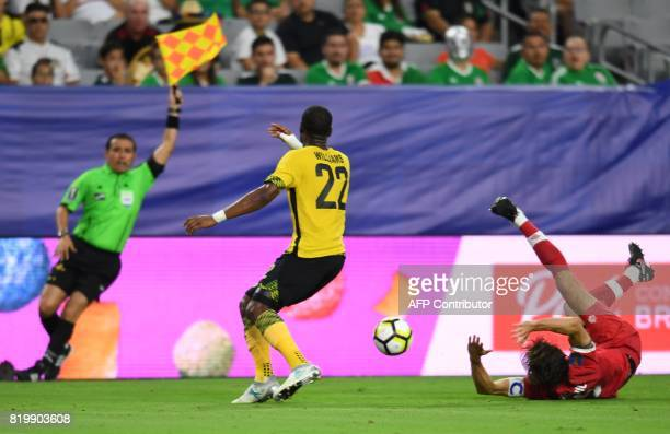 Jamaica's Romario Williams looks on as the referee raises a flag after he fought for the ball with Canada's Dejan Jakovic during their 2017 CONCACAF...