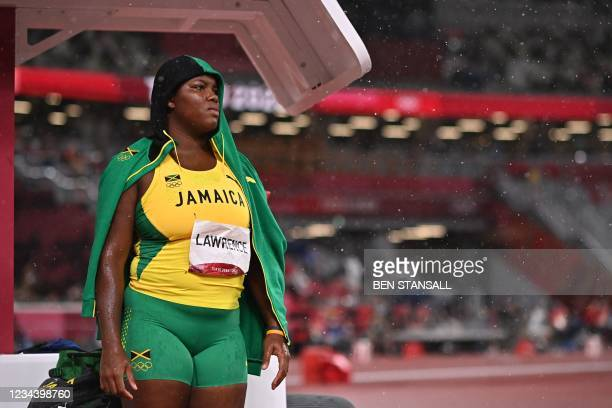 Jamaica's Shadae Lawrence shelters from the rain during the women's discus throw final during the Tokyo 2020 Olympic Games at the Olympic Stadium in...