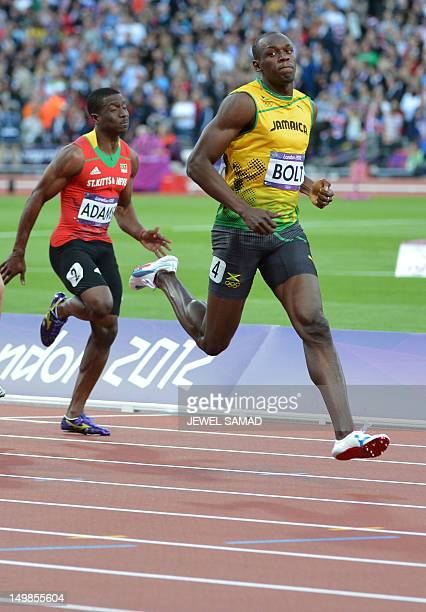Jamaica's Usain Bolt and Saint Kitts Nevis' Antoine Adams competes in the men's 100m semifinals at the athletics event during the London 2012 Olympic...