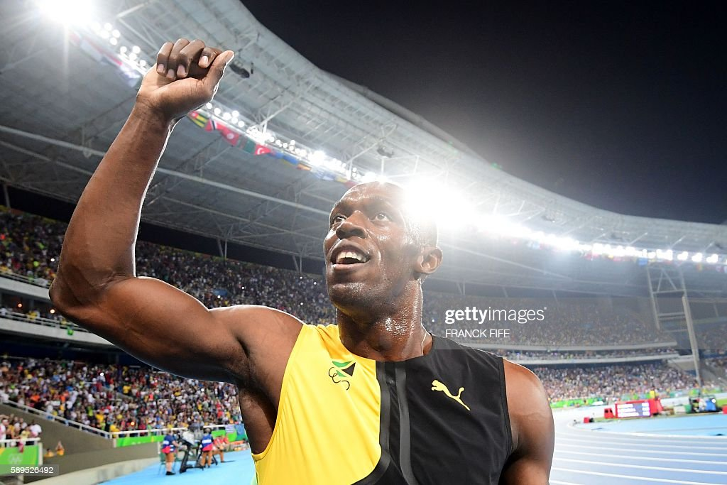TOPSHOT - Jamaica's Usain Bolt celebrates after he won the Men's 100m Final during the athletics event at the Rio 2016 Olympic Games at the Olympic Stadium in Rio de Janeiro on August 14, 2016. / AFP / FRANCK