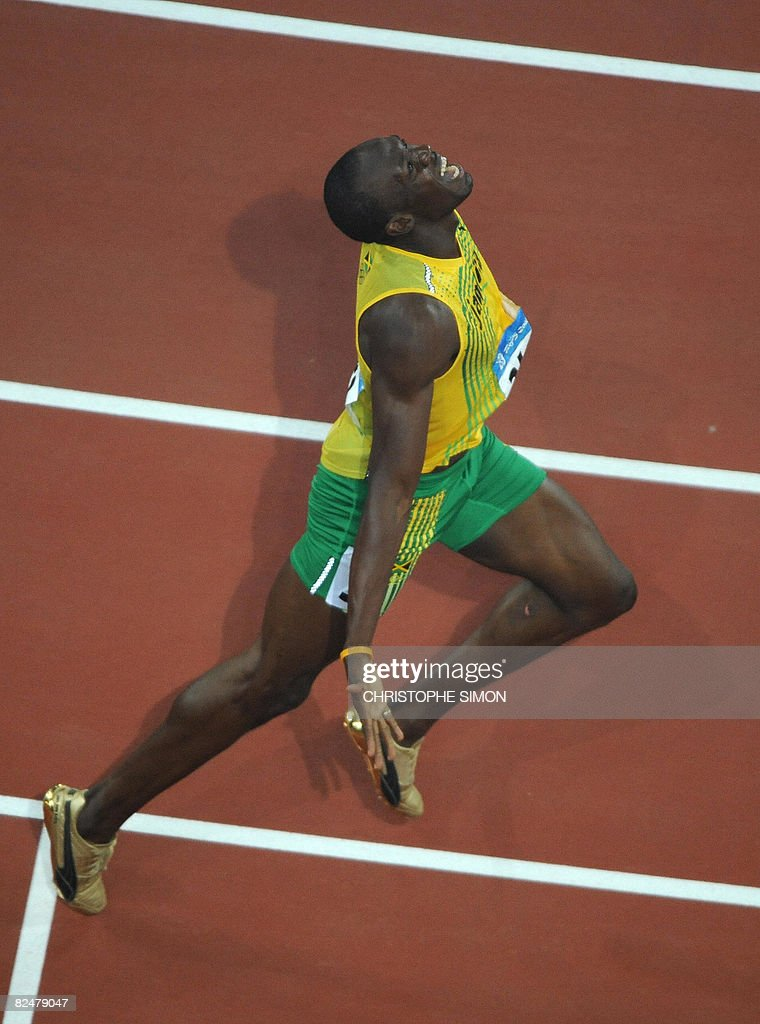 Jamaica's Usain Bolt celebrates as he crosses the finish line to win the men's 200m final at the National stadium as part of the 2008 Beijing Olympic Games on August 20, 2008. Bolt broke the men's 200 metres world record timing 19.30 seconds as he clinched the Olympic Games gold to add to his 100m crown. He won ahead of Churandy Martina of the Dutch Antilles and Shawn Crawford of the US.
