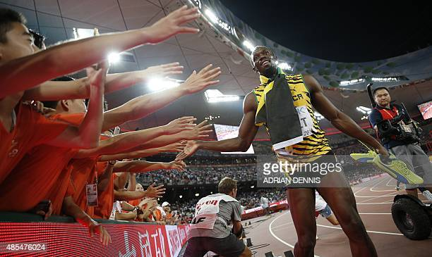 Jamaica's Usain Bolt celebrates next to a cameraman on a segway moments before the latter crashed into him after the final of the men's 200 metres...