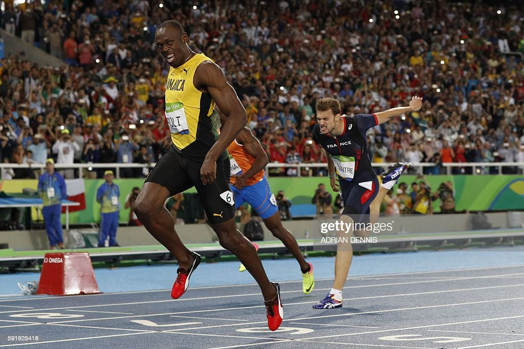 TOPSHOT - Jamaica's Usain Bolt celebrates winning the Men's 200m Final ahead of bronze medallist France's Christophe Lemaitre during the athletics event at the Rio 2016 Olympic Games at the Olympic Stadium in Rio de Janeiro on August 18, 2016. / AFP / Adrian DENNIS