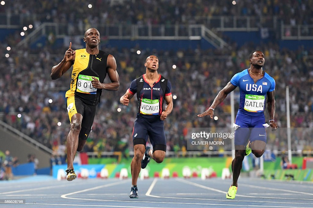 TOPSHOT - Jamaica's Usain Bolt (2ndL) crosses the finish line after he competed with France's Jimmy Vicaut (2ndR) and USA's Justin Gatlin to win the Men's 100m Final during the athletics event at the Rio 2016 Olympic Games at the Olympic Stadium in Rio de Janeiro on August 14, 2016. / AFP / OLIVIER