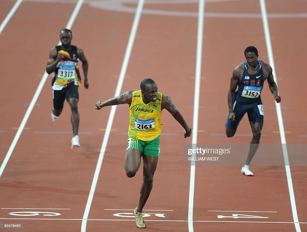 Jamaica's Usain Bolt (C) crosses the finish line ahead of Shawn Crawford of the US (R) to win the men's 200m final at the National stadium as part of the 2008 Beijing Olympic Games on August 20, 2008. Bolt broke the men's 200 metres world record timing 19.30 seconds as he clinched the Olympic Games gold to add to his 100m crown. He won ahead of Churandy Martina of the Dutch Antilles and Shawn Crawford of the US.