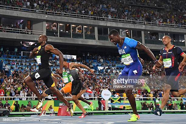 TOPSHOT Jamaica's Usain Bolt crosses the finish line ahead of silver medallist USA's Justin Gatlin and bronze medallist Canada's Andre De Grasse in...