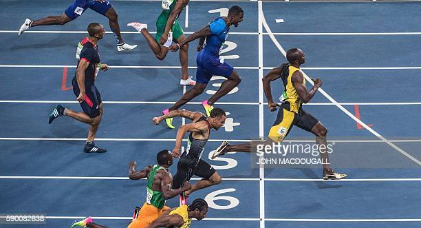 Jamaica's Usain Bolt crosses the finish line ahead of USA's Justin Gatlin to win the Men's 100m Final during the athletics event at the Rio 2016...