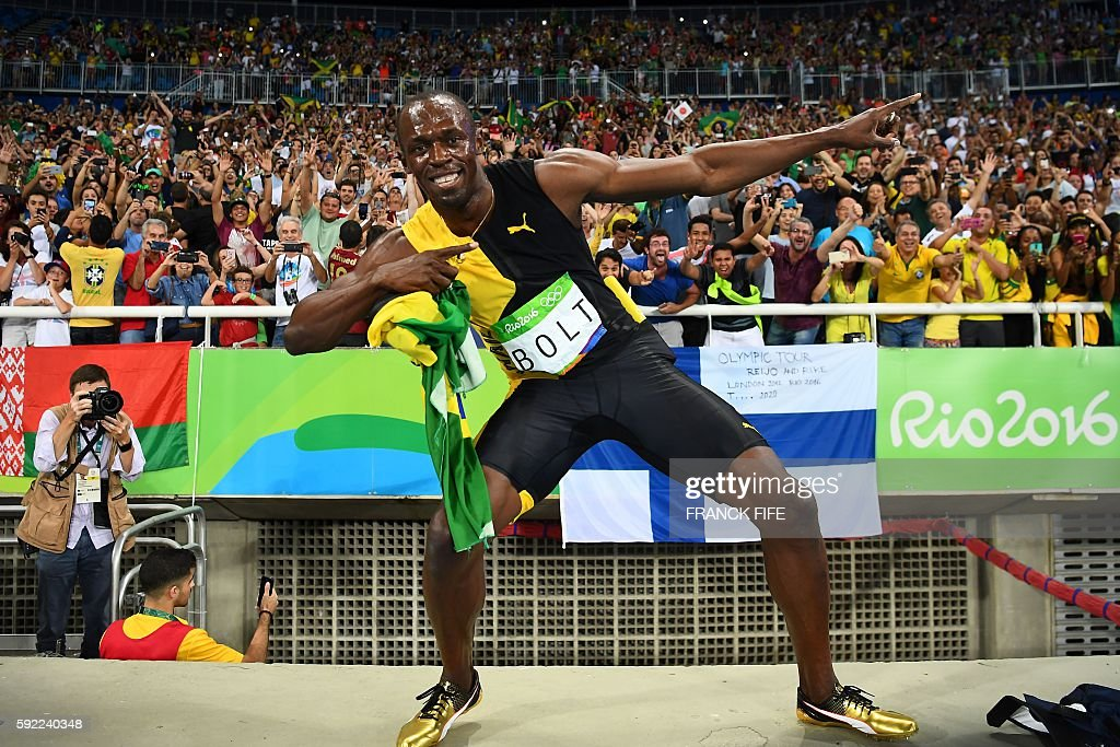 TOPSHOT - Jamaica's Usain Bolt does his 'Lightening Bolt' pose after Team Jamaica won the Men's 4x100m Relay Final during the athletics event at the Rio 2016 Olympic Games at the Olympic Stadium in Rio de Janeiro on August 19, 2016. / AFP / FRANCK