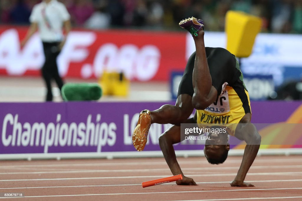 TOPSHOT - Jamaica's Usain Bolt falls after injuring himself in the final of the men's 4x100m relay athletics event at the 2017 IAAF World Championships at the London Stadium in London on August 12, 2017. /