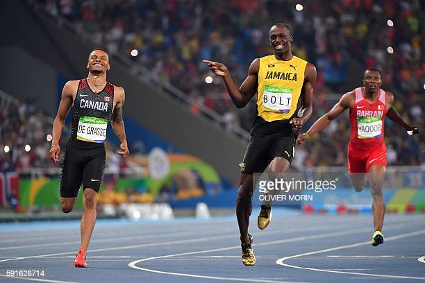 TOPSHOT Jamaica's Usain Bolt jokes with Canada's Andre De Grasse after they crossed the finish line in the Men's 200m Semifinal during the athletics...