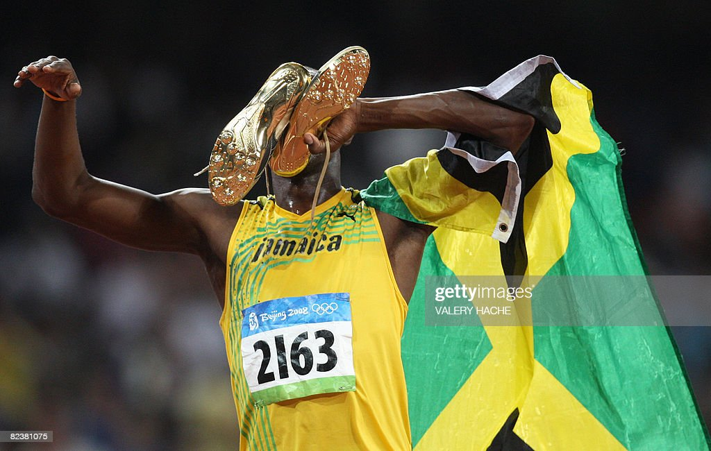 5eb7f813493 Jamaica s Usain Bolt kisses his shoes as he celebrates after winning ...