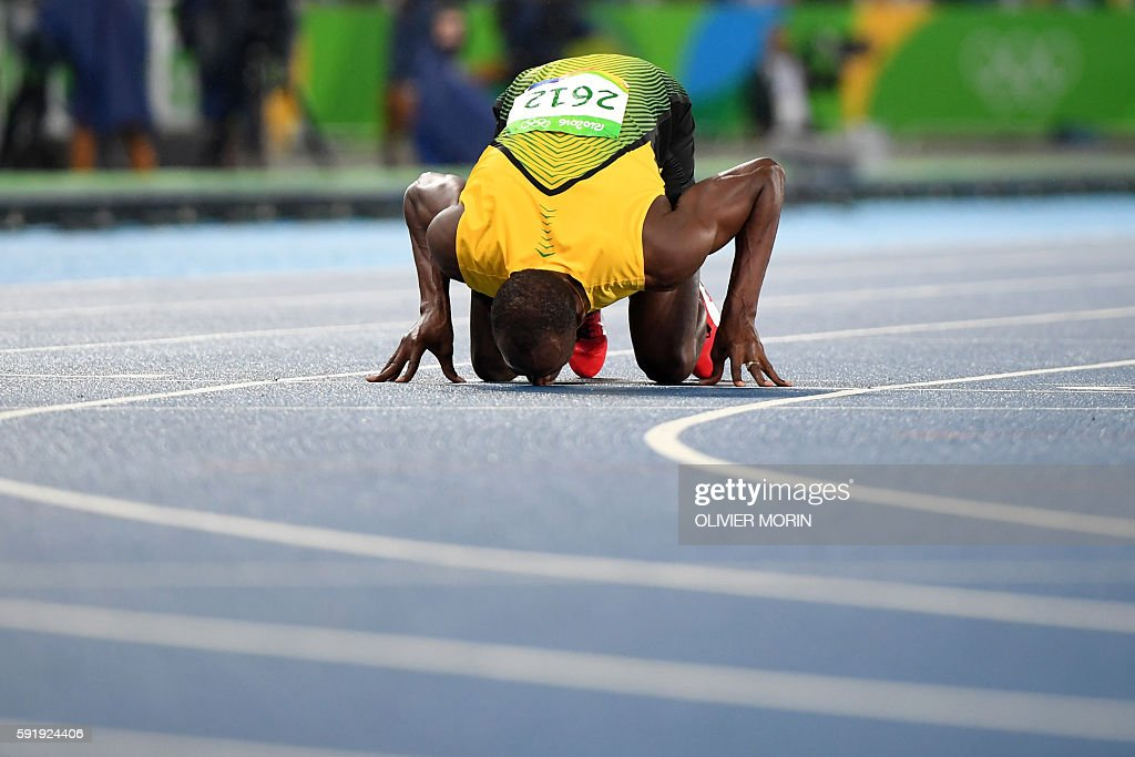 TOPSHOT - Jamaica's Usain Bolt kisses the track after he won the Men's 200m Final during the athletics event at the Rio 2016 Olympic Games at the Olympic Stadium in Rio de Janeiro on August 18, 2016. / AFP / OLIVIER