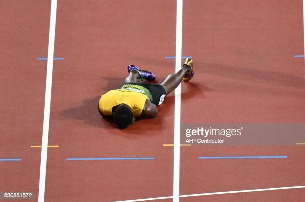 TOPSHOT Jamaica's Usain Bolt lies on the track after injuring himself during the final of the men's 4x100m relay athletics event at the 2017 IAAF...