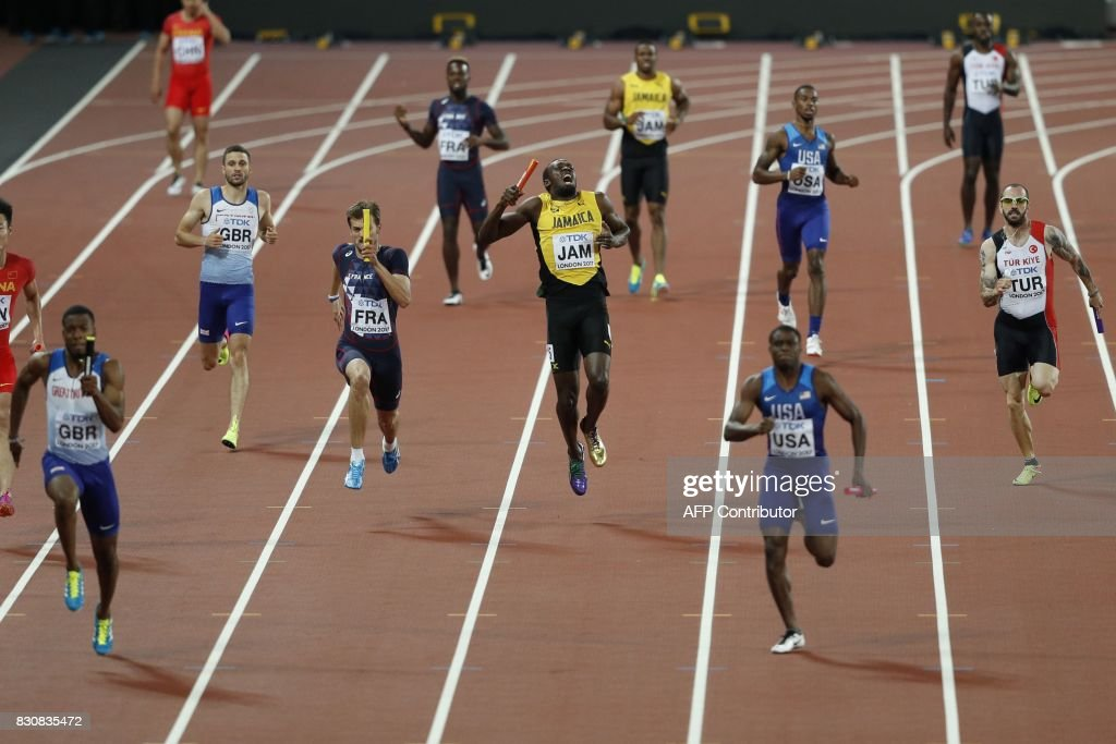 Jamaica's Usain Bolt (C) pulls up injured in the final of the men's 4x100m relay athletics event at the 2017 IAAF World Championships at the London Stadium in London on August 12, 2017. / AFP PHOTO / Adrian DENNIS