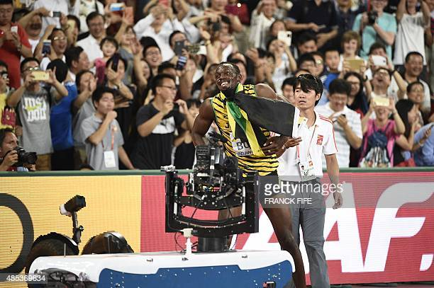 Jamaica's Usain Bolt reacts after a cameraman on a segway crashed into him in the final of the men's 200 metres athletics event at the 2015 IAAF...
