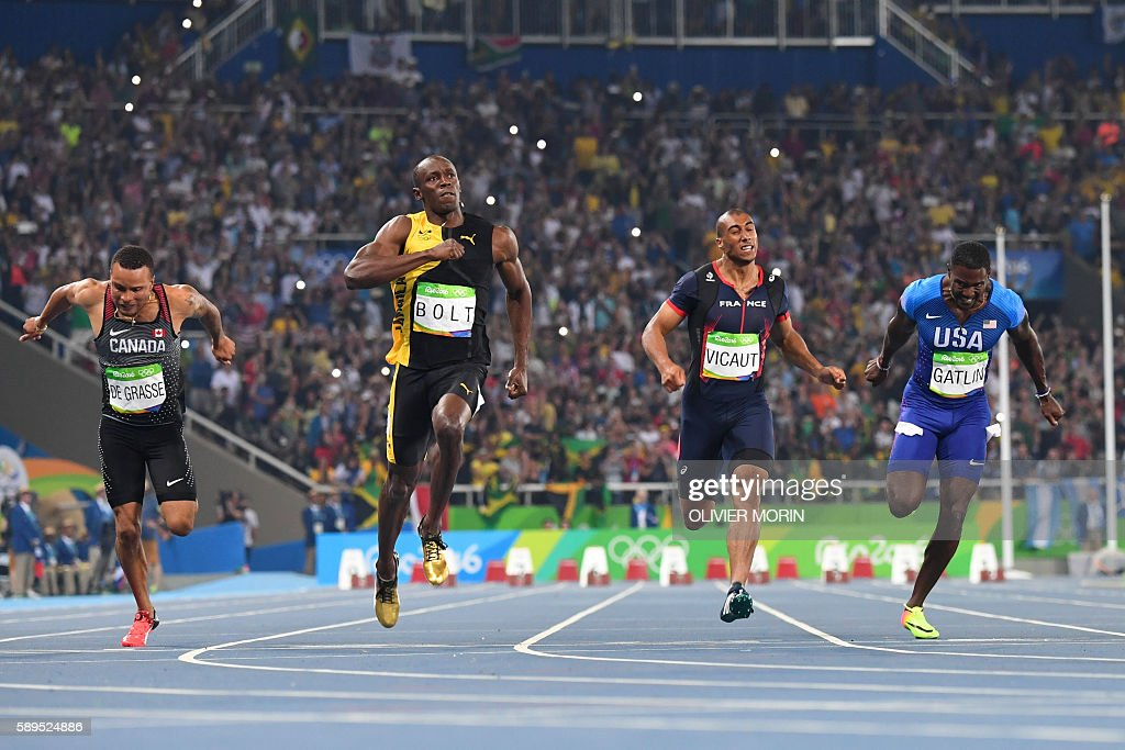 TOPSHOT - Jamaica's Usain Bolt (2ndL) reacts after he crossed the finish line head of USA's Justin Gatlin (R), Canada's Andre De Grasse (L) and France's Jimmy Vicaut to win the Men's 100m Final during the athletics event at the Rio 2016 Olympic Games at the Olympic Stadium in Rio de Janeiro on August 14, 2016. / AFP / OLIVIER